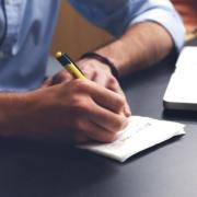 Mans d'un home escrivint a una llibreta. Hi ha un ordinador Mac de fons.